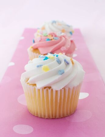small plate: Cupcake with pink and white icing Stock Photo