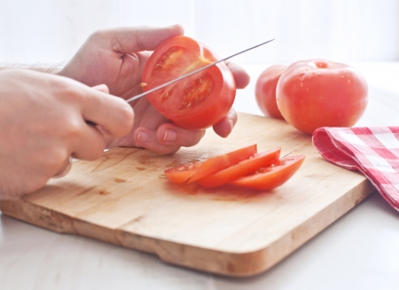 man cutting tomato  photo