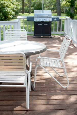 lawn chair: Grill and table on porch deck Stock Photo