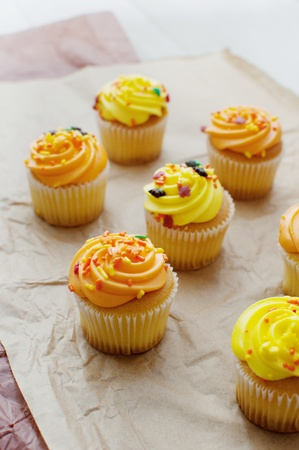 Yellow and orange cupcakes with icing vertical photo