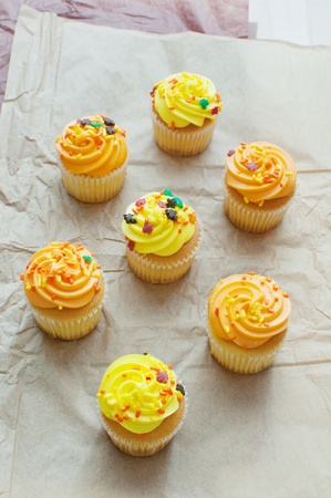 Cupcakes top view with orange and yellow frosting vertical photo