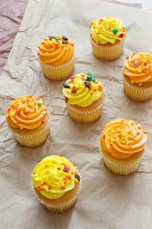 Seasonal cupakes in yellow and orange with sprinkles top view photo