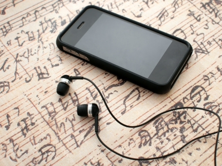 Earphones and phone on music sheet background horizontal photo