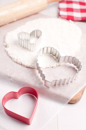 Dough and cookie cutters for making valentine days treats vertical photo