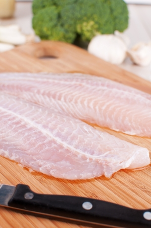 Two raw white fish fillet and knife vertical