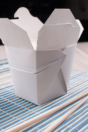 unprinted: White box with rice from chinese takeout with chopsticks