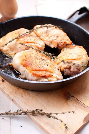 Fried golden chicken thighs with spices and herbs photo