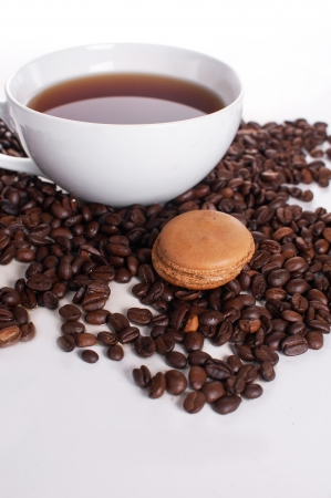 Coffee macaroon cookie and a cup on white photo