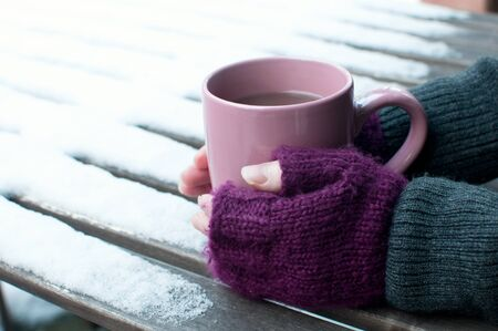 Cup of cocoa outdoors in winter and purple mittens photo