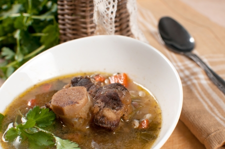 meat soup: Ox tail soup with barley and parsley close-up Stock Photo