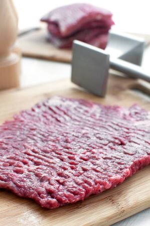 pounder: Raw beef round steak and meat pounder