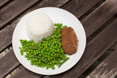 Cutlet dinner with white rice and green peas photo