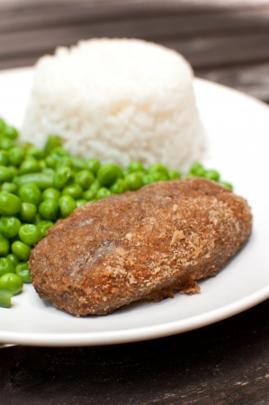 Breaded cutlet with rice and green peas salad photo