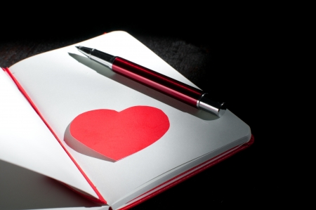 Dramatic notepad page with heart shape and pen photo
