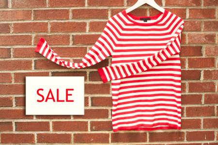 invitando: Camisa a rayas rojas y blancas que invitan a firmar la venta Foto de archivo