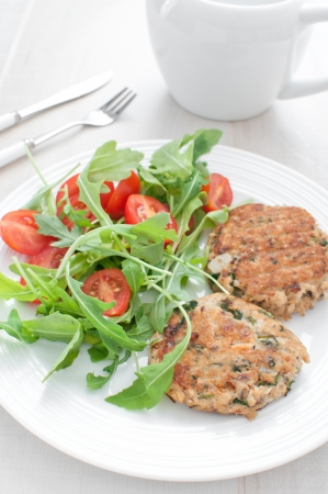 Fish patties with parsley and arugula tomato salad dinner