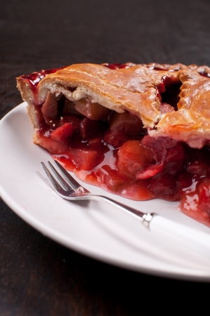 Eating rhubarb and strawberry tart pie with fork photo