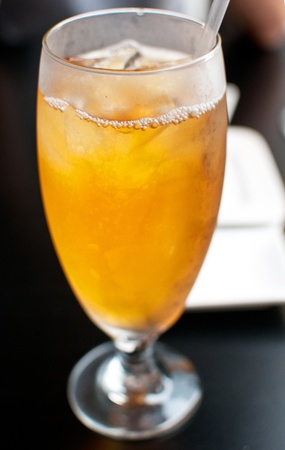 Glass of iced tea with straw on black table photo