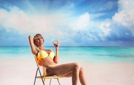 Young beautiful woman enjoying the sun on the beach photo