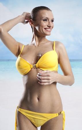 yellow bikini: Young beautiful woman enjoying the sun on the beach