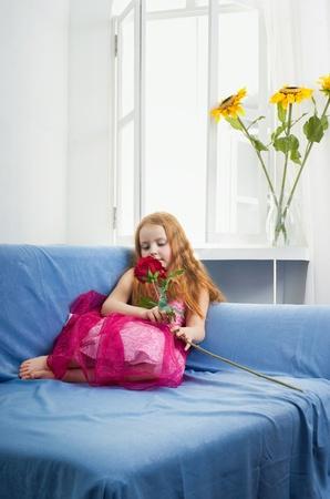 Little girl on a sofa near the window Stock Photo - 13507464