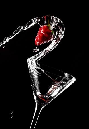 copa de martini: C�ctel de fresa derrame de la copa Foto de archivo