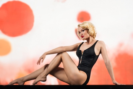 Blonde in black swimsuit on colored background photo