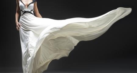 White fluttering dress on black background