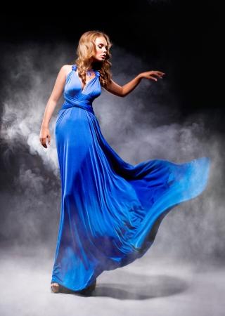 Elegant meisje in fladderende blauwe jurk