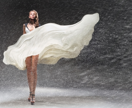 Girl in fluttering dress in the snow photo