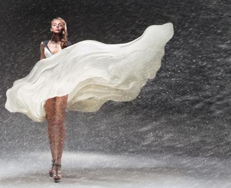 Meisje in fladderende jurk in de sneeuw Stockfoto
