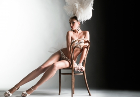 Seductive dancer sitting on the chair Stock Photo