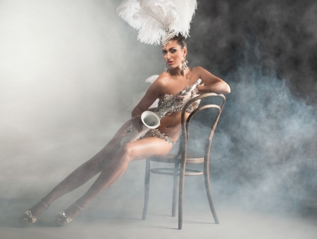 Seductive dancer with saxophone sitting on the chair photo