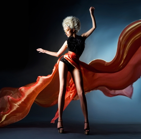 Heldere blonde in wapperende rode rok Stockfoto