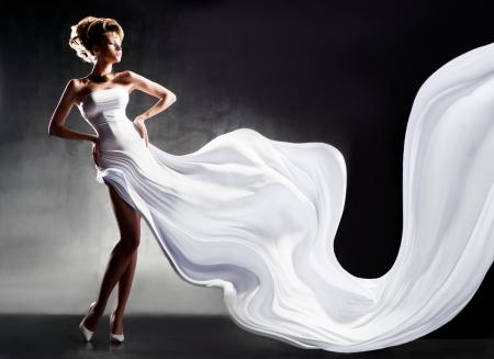 Mooi meisje in fladderende witte jurk