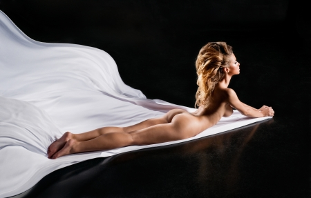 Beautiful sexual girl lies on silk