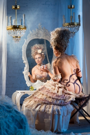 Actress sitting in the dressing room with perfume photo