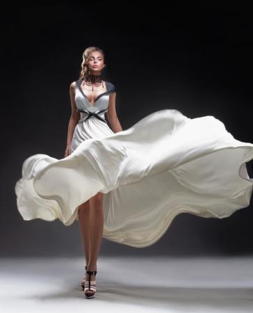 Mooie blonde in fladderende jurk Stockfoto