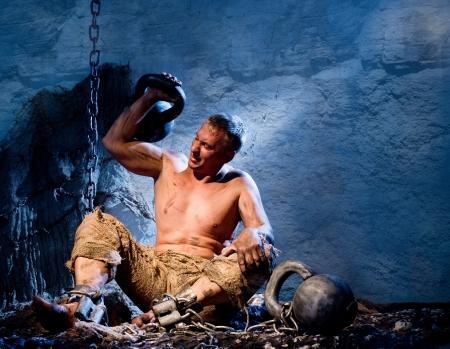 malefactor: Prisoner in heavy shackles raises the weight