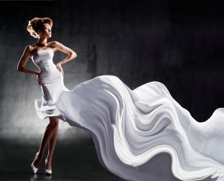 Aantrekkelijk meisje in fladderende witte jurk