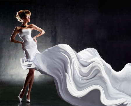 Attractive girl in fluttering white dress