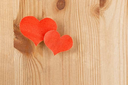 Wooden background with paper hearts photo