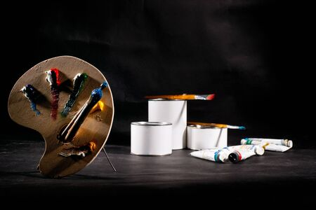Palette and paint cans on the table photo