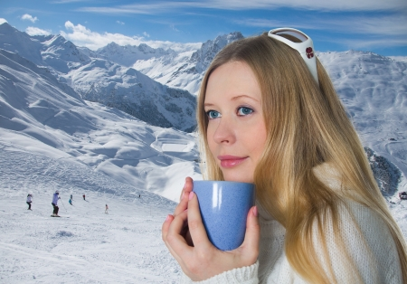 Blonde with a mug on background of the mountains photo