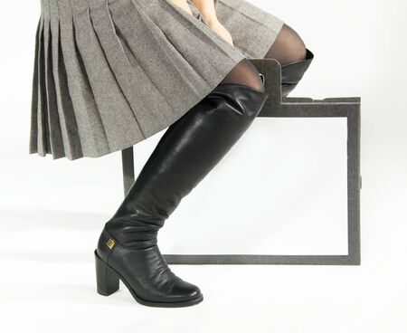 Black boots, pleated skirt and bag photo