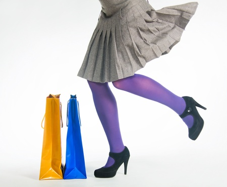 pleated: Female legs and colored bags Stock Photo