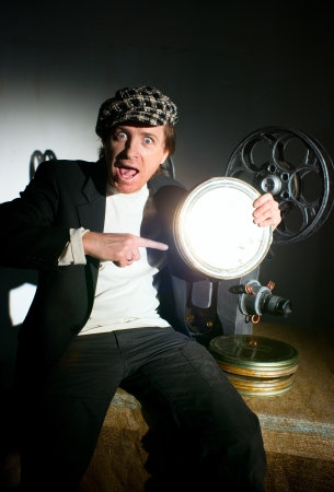 Funny projectionist and film projector with film photo