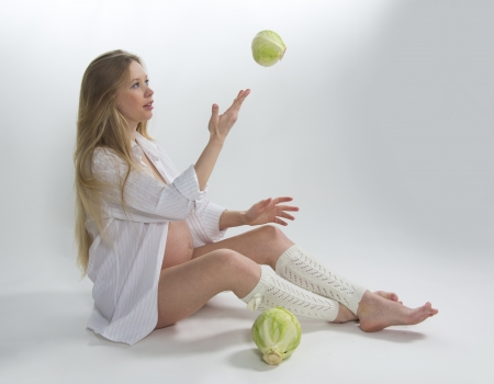 Portrait of pregnant blonde with green cabbage Stock Photo