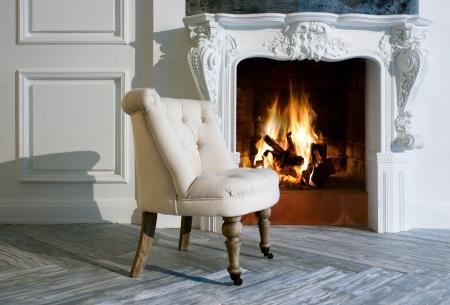 ohniště: Bílé křeslo u krbu Reklamní fotografie
