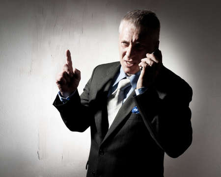 Serious businessman with a cellular phone photo